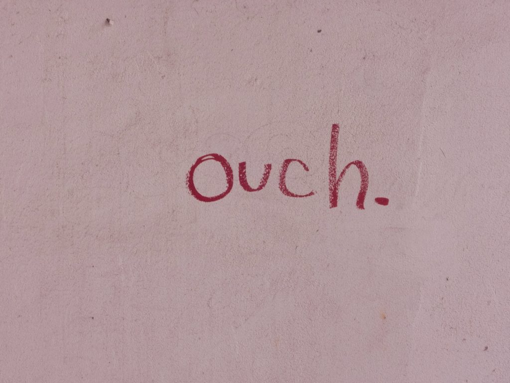 Pink wall with red text which says ouch. Text looks like it has been written in lipstick