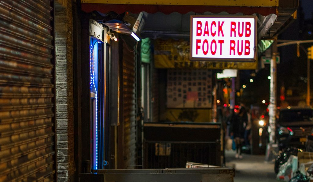 Sign for Back Rub and Foot Rub in dark street