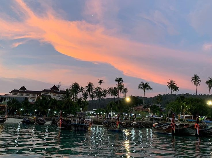 Photo shows sunset with blue and orange sky, over Phi Phi Pier, with water and palm trees