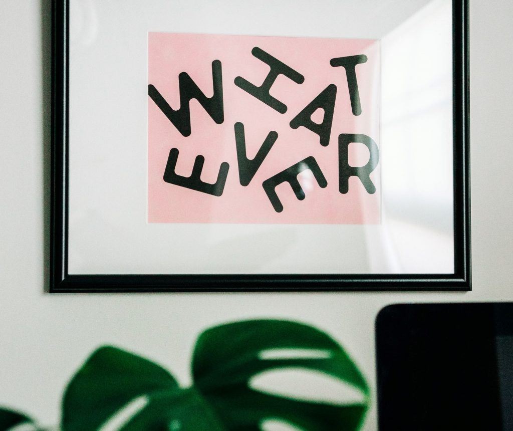 White wall with frame on. Frame contains picture of white square with smaller pink square in the foreground. The word 'whatever' is written in a wonky pattern. In the foreground of the photo is an unfocused plant