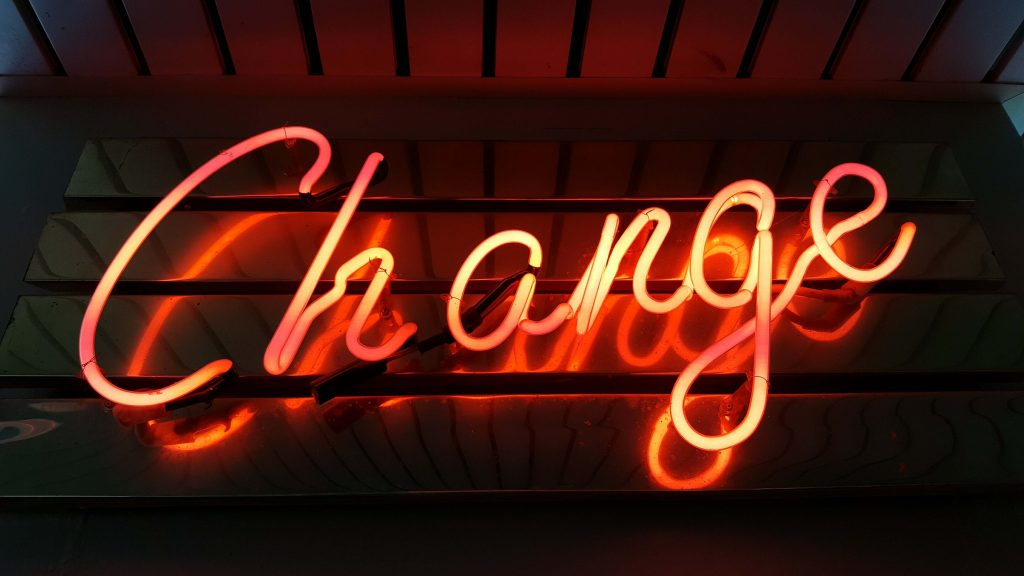 Orange neon sign of the word Change on black background
